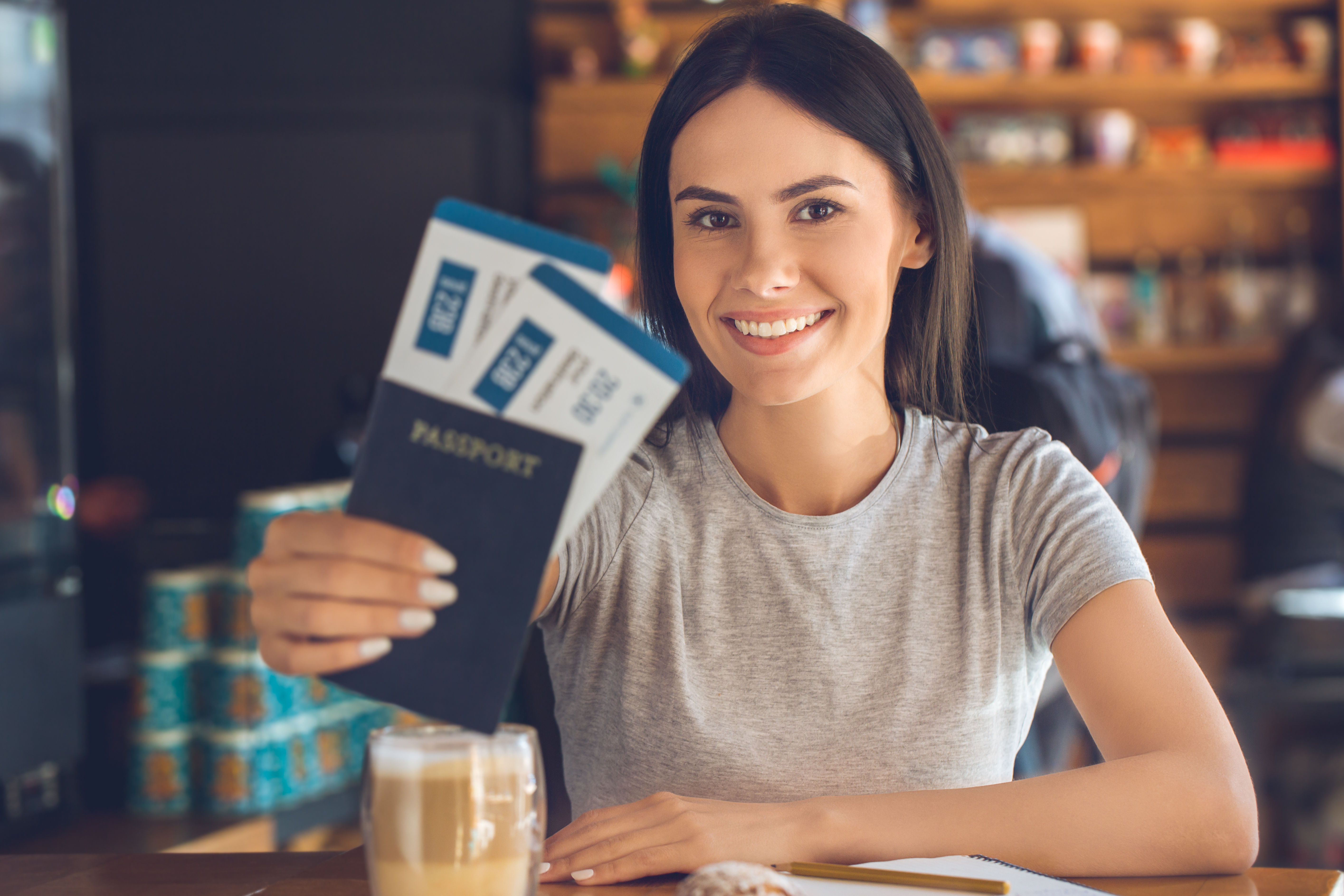 woman sitting in a coffee shop with passport