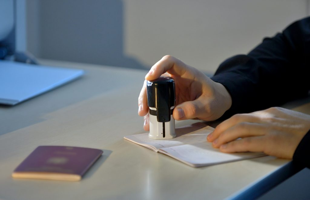 Customs Officer Stamping a Passport