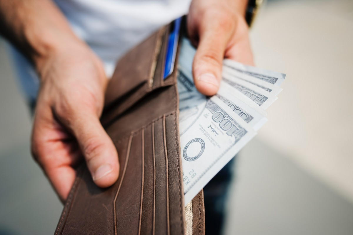 Man Holding an purse full of currency