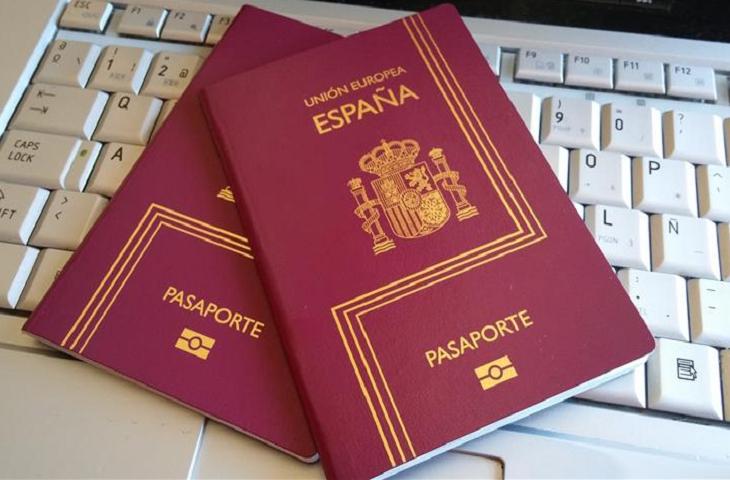 Spain passport laid on the Laptop