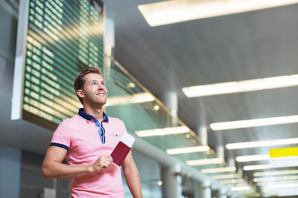 Traveling man at the airport with passport