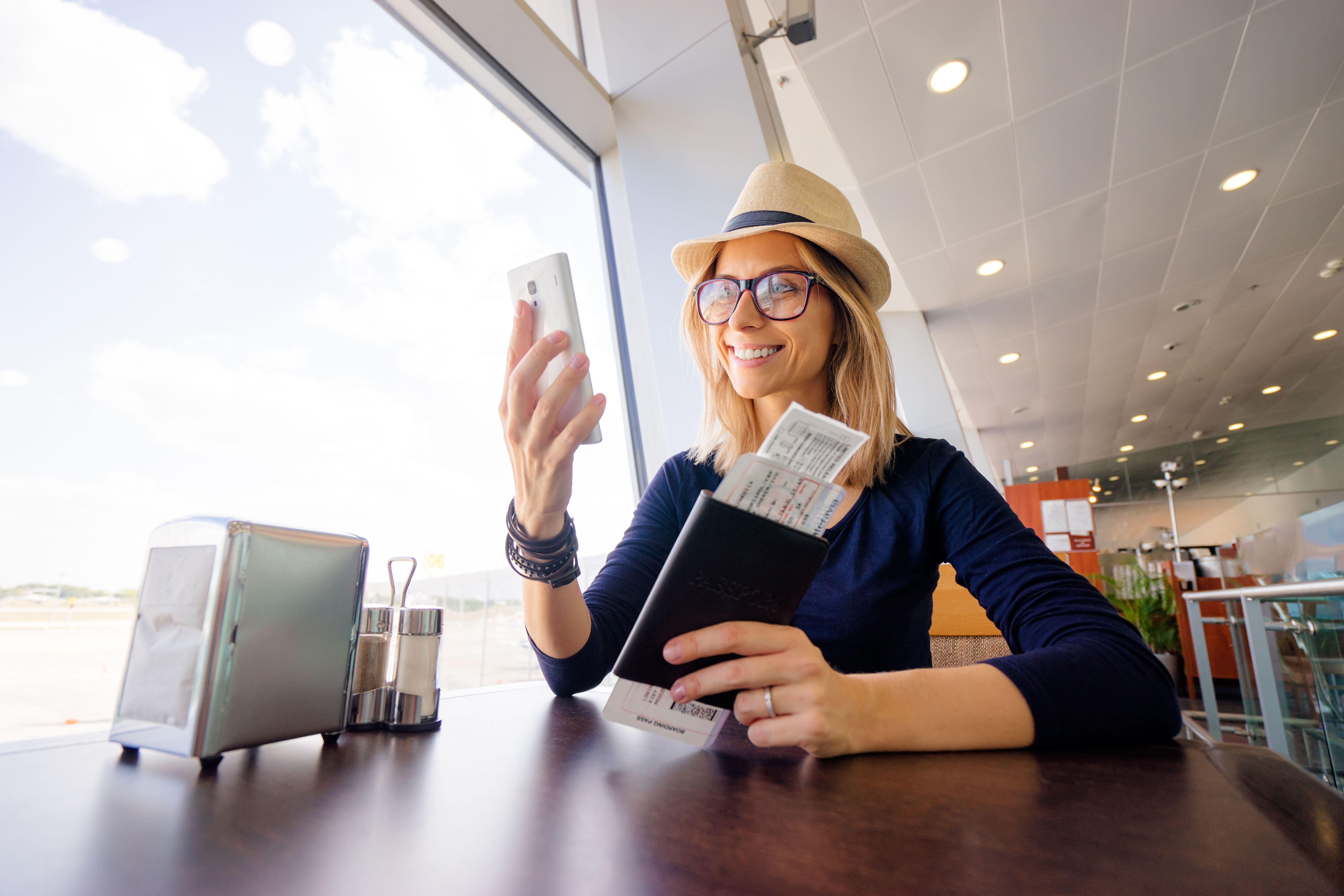 Woman using smartphone with passport on her hand
