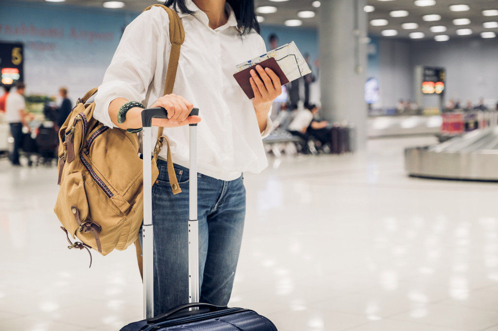 woman at Airport with passport and Luggages