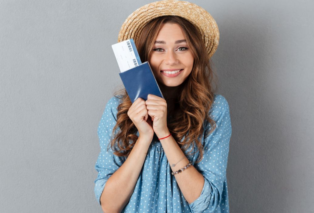 woman wearing hat and holding passport