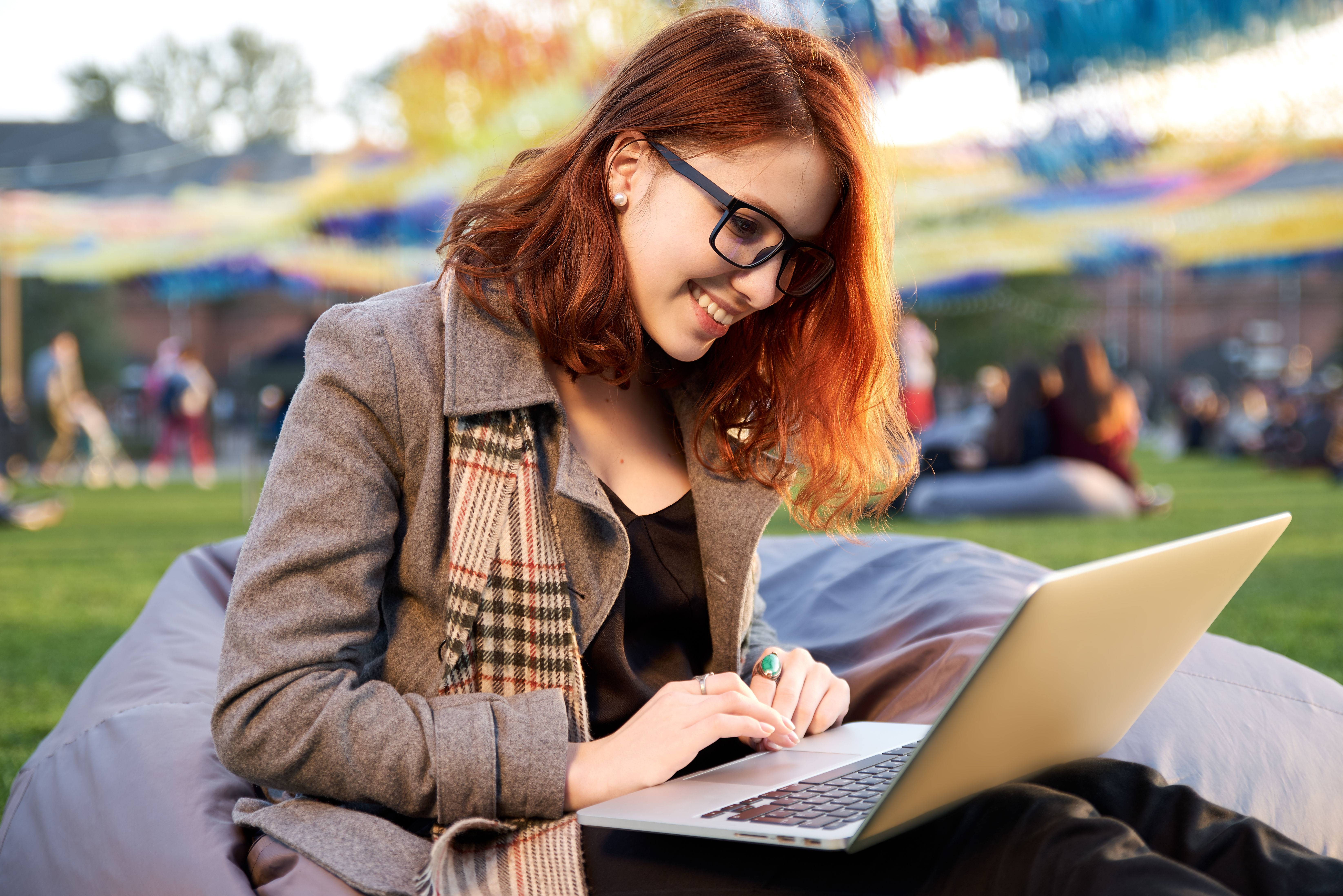 young red haired woman in glasses with a laptop