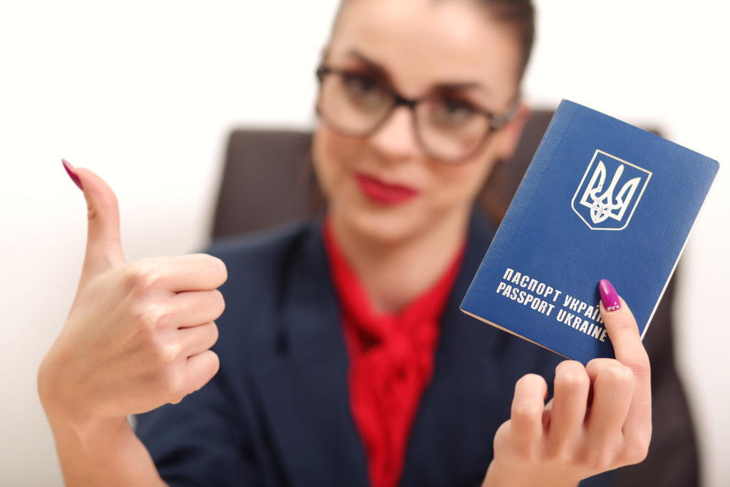 Beautiful young woman holding a passport Ukraine and raised thumb up