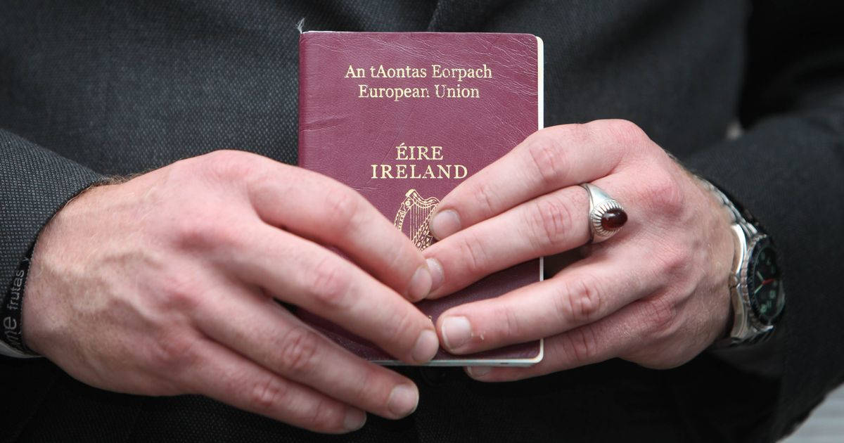 Man holding the Ireland Passport in his hand
