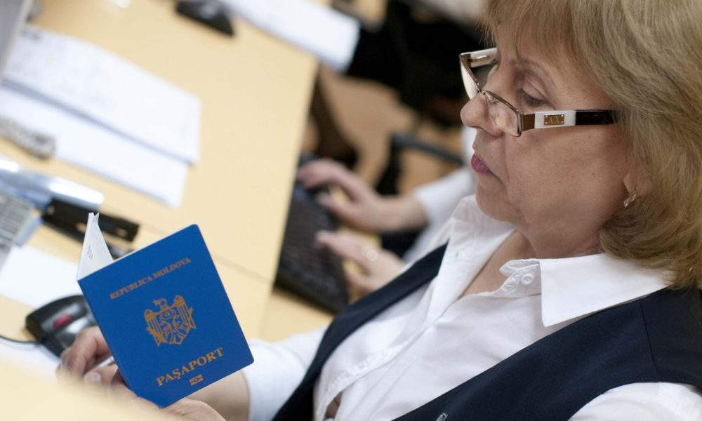 Passport Officer looking on the Moldova citizen Passport