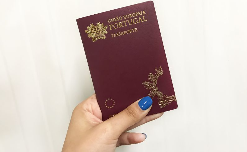 Women holding the portugal Passport in hand
