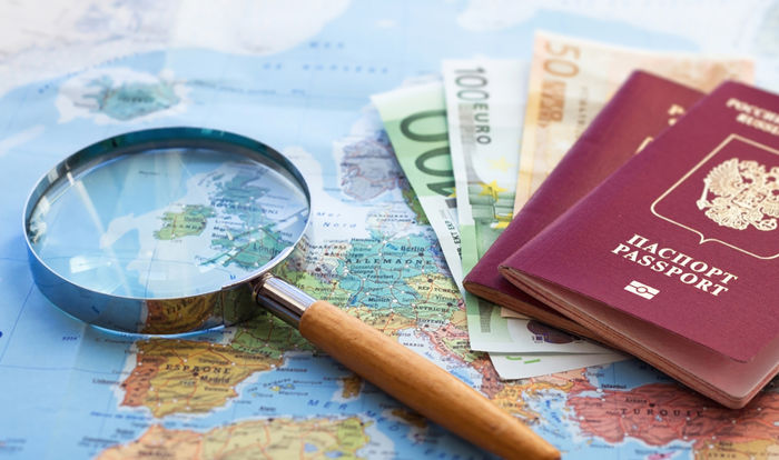 magnify glass along with passport placed on Map