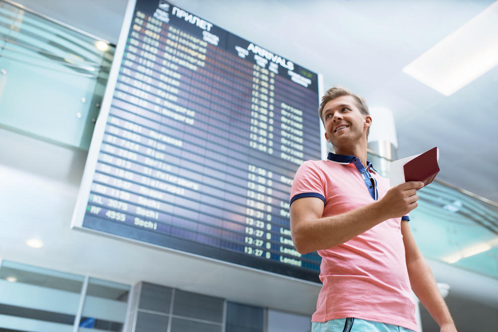 Smiling man with a passport at the board